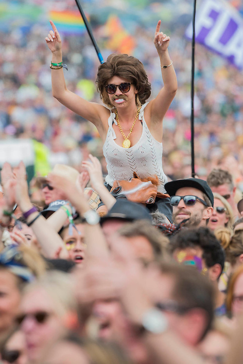 Enthusiastic fans, many sporting wigs and of false beards (and even teeth, the pay homage to the era. Barry Gibb of the Bee Gees plays the Pyramid Stage - The 2017 Glastonbury Festival, Worthy Farm. Glastonbury, 25 June 2017