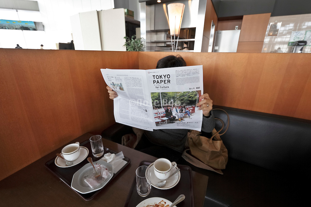 Reading the Tokyo paper while drinking a coffee
