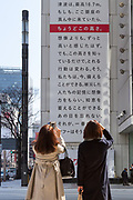 Two women look at a  large billboard on the side of the Sony Building in Ginza marks the sixth anniversary of the March 11th 2011 earthquake and tsunami in Tohoku. Ginza, Tokyo, Japan. Friday March 10th 2017 The billboard was created by Yahoo and shows the asks passers by to remember the disaster and the nearly 16,000 people who died. the line marked in red shows the maximum height of the tsunami (16.7 metres at Ofunato in Miyagi prefecture. The billboard is on display until March 12th.