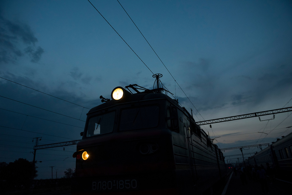 A locomotive moves slowly through a station in central Ukraine at night