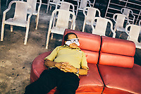 An older Thai man takes a nap before the fights at Thepprasit Stadium in Pattaya, Thailand.