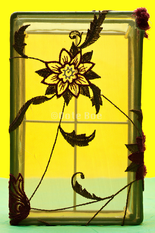 empty basket with clear netting and flower embroidery object on yellow green background