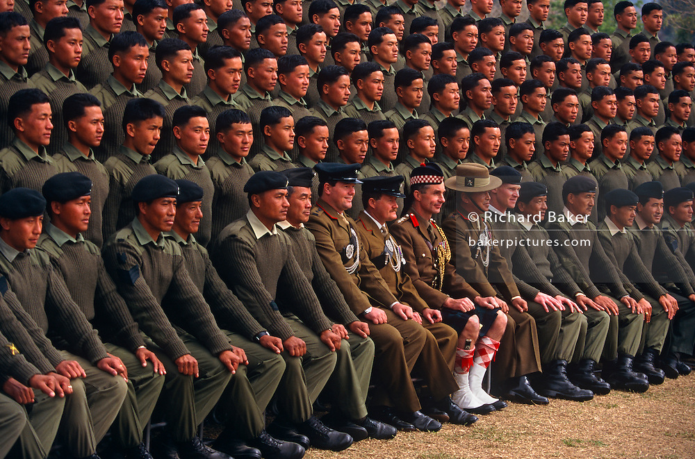 Officers and new recruits of the British Royal Gurkha Regiment pose for their official photograph at their army camp at Pokhara, Nepal after recently being recruited into the regiment after a gruelling series of tests to eliminate the weaker and less able candidates, before the 160 lucky candidates travel to the UK for basic training. 60,000 boys aged between 17-22 (or 25 for those educated enough to become clerks or communications specialists) report to designated recruiting stations in the hills each November, most living from altitudes ranging from 4,000-12,000 feet. After initial selection, 7,000 are accepted for further tests from which 700 are sent down here to Pokhara in the shadow of the Himalayas. Only 160 of the best boys succeed in the journey to the UK. Nepal has been supplying youth for the British army since the Indian Mutiny of 1857..