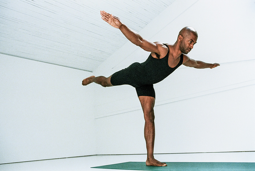 A man doing yoga airplane pose in a white room.