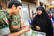 07 JULY 2013 - NARATHIWAT, NARATHIWAT, THAILAND: A Royal Thai Marine medic gives a Thai Muslim woman medicine at a Marine wellness clinic in Narathiwat. Royal Thai Marines in Narathiwat province held a special ceremony Sunday in advance of Ramadan. They presented widows, orphans and indigent people with extra rice and food as a part of the Thai government's outreach to resolve the Muslim insurgency that has wracked southern Thailand since 2004. The Holy Month of Ramadan starts on about July 9 this year. Muslims are expected to fast from dawn to dusk, engage in extra prayers, recitation of the Quran and perform extra acts of charity during Ramadan. It is the holiest month of the year for Muslims.    PHOTO BY JACK KURTZ