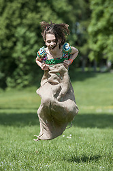 Girl jumping in sack race in a field, Munich, Bavaria, Germany