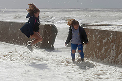 © Licensed to London News Pictures. 25/08/2020. Porthcawl, Bridgend, Wales, UK. People enjoy the foam on the promenade as Storm Francis batters the small Welsh seaside resort of Porthcawl in Bridgend, UK. with severe gale force winds and massive waves. Photo credit: Graham M. Lawrence/LNP