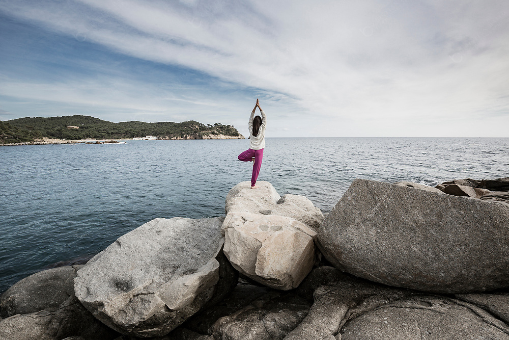 Young woman doing tree pose at the sea