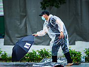 24 OCTOBER 2017 - BANGKOK, THAILAND: A man wearing a rain poncho picks up a black umbrella with a black ribbon on it, the umbrella for people mourning the Late King, while he waits on Atsadang Rd to get into the royal cremation site. People started camping out along Atsadang Road in Bangkok near the royal cremation site on Monday. The gates won't open until Wednesday morning and the cremation isn't until Thursday night, so most people will sleep outside, on sidewalks and footpaths for three nights. Hundreds of thousands of people are expected to try to get into Sanam Luang, the site of the cremation of Bhumibol Adulyadej, the Late King of Thailand, but the site will only hold about 60,000 people. The Thai government has built replica crematoriums around Bangkok to accommodate the overflow crowds.        PHOTO BY JACK KURTZ
