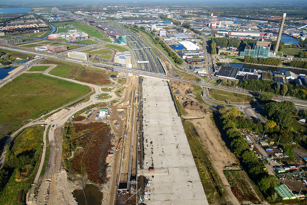 Nederland, Utrecht, Utrecht, 24-10-2013; Rijksweg A2 en de noordelijke ingang van de  Leidsche Rijntunnel. De landtunnel moet de verkeersoverlast, luchtvervuiling en geluidsoverlast voor Utrecht en de Vinexwijk Leidsche Rijn (l) moet verminderen. Op het betonnen dak komt een park. Rechts het Amsterdam-Rijnkanaal met de stad Utrecht. <br /> Roadway A2 and the northern entrance to the tunnel Leidsche Rijn, a landtunnel built to decrease the nuisance of traffic noise and air pollution for the city of Utrecht and the suburb Leidsche Rijn (l) . A park will be build on the concrte roof. Right the Amsterdam-Rhine Canal and the city of Utrecht.<br /> luchtfoto (toeslag op standaard tarieven);<br /> aerial photo (additional fee required);<br /> copyright foto/photo Siebe Swart.
