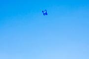 Blue plastic bag being wind swept across the big blue sky in London, United Kingdom.