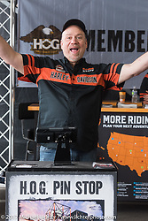 HOG regional rep Bruce Motta gets visitors their free Daytona pins at the Pin-Stop booth at the Harley-Davidson display at the Daytona Speedway during Daytona Bike Week. Daytona Beach, FL. USA. Monday March 13, 2017. Photography ©2017 Michael Lichter.