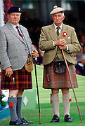 Two traditional Scotsmen wearing tartan kilts, tweed jackets, caps, sporrans and holding walking sticks at the Braemar Games, a Royal Highland gathering.