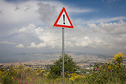 Warning sign of risk on the western slope of Vesuvius with the urban sprawl of Naples in the distance.