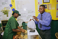 Woman working in Caribbean café serving customer,