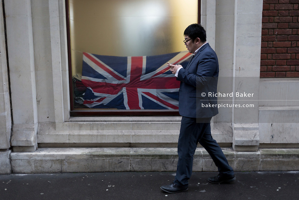 An Asian businessman walks past a crumpled British Union Jack flag in the window of a City retailer, on 2nd February 2017, in the City of London, England.