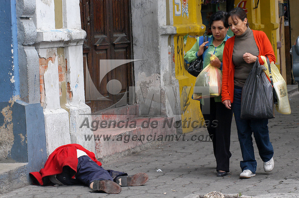 Toluca, Mex.- Unas mujeres pasan a un costado de un indigente que duerme en la via publica. Agencia MVT / Hernan Vazquez. (DIGITAL)<br /> <br /> NO ARCHIVAR - NO ARCHIVE