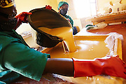 Women pour liquid shea butter soap into a mold at the Si Yiriwa shea processing center in the town of Diolila, Mali on Friday January 15, 2010.