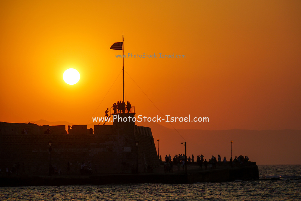 The Venetian era harbour walls and lighthouse at the Mediterranean port of Rethymnon, Crete, Greek Islands, Greece, Europe at sunset