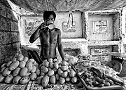 Seller of mangoes and chicken tries to cool off  with a mug of water protected by a canvas already aged by scorching sun. The graves stand on the background, as if they didn´t existed for him.