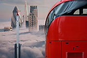 The rear of a red London Routemaster bus beneath a property developer's billboard showing a large aerial image of London skyscrapers in low cloud on Shoreditch High Street showing a large aerial image of London skyscrapers in low cloud. This site will be called Principal Place, a new 15-storey office block designed by Foster and Partners in Worship Street, Shoreditch, London. The mural image shows some of the capital's best-known tall buildings that rise above the fog - now a very unusual weather phenomenon after thick fogs in the 1950s.