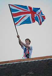 © Licensed to London News Pictures. 03/06/2012. London, UK. A man waving the union flag from a rooftop during Diamond Jubilee pageant celebrations in London on June 03, 2012. Great Britain is celebrating the 60th  anniversary of the countries Monarch HRH Queen Elizabeth II accession to the throne . Photo credit : Ben Cawthra/LNP