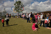 Spectators queue for the privilege to pose for family photos under giant IOC Olympic rings on a hill in the Olympic Park during the London 2012 Olympics. This land was transformed to become a 2.5 Sq Km sporting complex, once industrial businesses and now the venue of eight venues including the main arena, Aquatics Centre and Velodrome plus the athletes' Olympic Village. After the Olympics, the park is to be known as Queen Elizabeth Olympic Park.