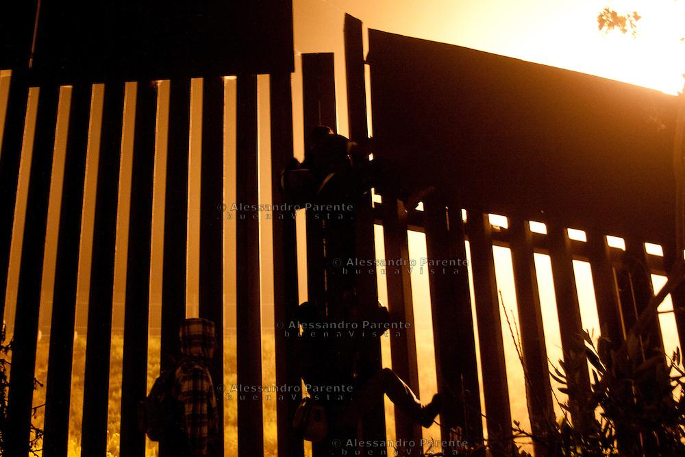 Gruppo di migranti scavalca la frontiera sperando di riuscire a percorrere i due chilometri che li separano da San Diego senza problemi.