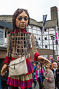 Little Amal, a giant puppet of a Syrian refugee girl fleeing conflict, arrives at the Globe Theatre from St Pauls Cathedral on 23rd October 2021 in London, United Kingdom. The 3.5-metre puppet, which is nearing the end of an 8,000km journey from the Turkish-Syrian border to Manchester in support of refugees, earlier climbed the steps of St Pauls Cathedral to present a wood carving of a ship at sea from St Pauls birthplace at Tarsus in Turkey to the dean.