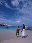 A mother holds her son's hand while walking along the beach in the British Virgin Islands