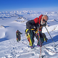 ANTARCTICA.  Norman Vaughan, 88, exhausted as he climbs towards summit on first ascent of Mount Vaughan, a 10,302-foot mountain near the South Pole that was named for him by Richard Byrd in honor of his participation in Byrd's 1929 expedition to fly over the Pole. He summit two days before his 89th birthday. Carolyn Muegge-Vaughan background. Trans-Antarctic Mountains.
