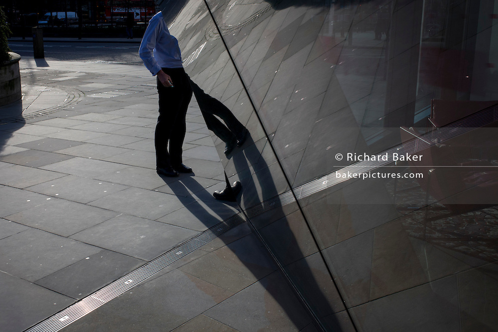 Angled smoker stands talking plus angled reflections in sheet glass of City office entrance.