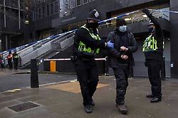 © Licensed to London News Pictures. 03/02/2021. London,UK. Police remove a protester. Bailiffs work to evict a group of eco-activists who are living in increasingly unstable tunnels beneath Euston Square Gardens in central London. The eviction of the HS2 Rebellion group from the square began one week ago and continues today.  Photo credit: Marcin Nowak/LNP