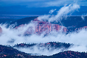 Low clouds and fog rise from between the ridges in Bryce Canyon National Park, Utah.