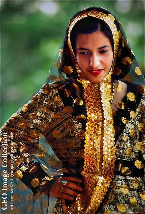 """A Bahraini woman wears an elaborate gold-lace robe to a family celebration.  While young women in all six Persian Gulf monarchies increasingly wear western clothes during their leisure time, most still adhere to a fairly strict uniform in public — the """"abaya,"""" or cloak."""