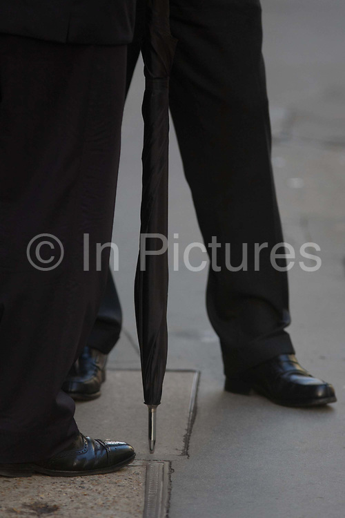 Two gentlemen discuss business in the street in the City of London. Standing together to talk, we see a detail of the sheos and legs of two businessmen - one holding his umbrella brolly to lean on. They remain anonymous as the busy life of the street continues around them during their quiet moment to speak about a deal or a contract outside. The City of London is the UK capital's financial heart, founded by the Romans in AD43.