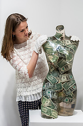 """© Licensed to London News Pictures. 08/06/2015. London, UK. A Sotheby's staff member looks at """"Venus aux dollars"""" by Arman (est. £16,000-22000), at the preview of """"To the Bearer on Demand"""", a private collection of 21 works inspired by the US dollar, including Andy Warhol masterpieces, which will be auctioned on 1 and 2 July.  The collection is estimated to realise £50 million. Photo credit : Stephen Chung/LNP"""
