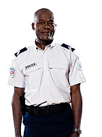 Portrait of an afro American mature policeman standing in studio on white isolated background