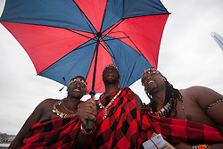 © licensed to London News Pictures. London, UK 01/01/2000. Lloyd Benson, Isaac Stephen and Abrajah Rafiq posing with an umbrella after handing out tea gift packages from Kenya to London commuters to celebrate Queen?s Diamond Jubilee this morning on London Bridge. Photo credit: Tolga Akmen/LNP