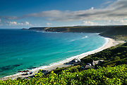 An elevated viewpoint over the emerald seas of Cornwall's stunning Sennen Cove. Cape Cornwall can be seen in the distance. Summer. England, UK.