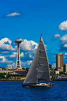A sailboat on Puget Sound passes in front of the Space Needle, Seattle, Washington USA.
