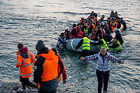 MYTILINI, GREECE - FEBRUARY 09: Volunteers guide refugees to safe zone arriving at Katia beach in a dinghy during the early morning on February 09, 2015 in Mytilini, Greece. Dozens of volunteers watch day and night on the beaches of Lesvos for the arrival of refugees. Volunteers are the firsts to help refugees that are not rescued by coastguards that watch the Aegean sea. Teams of doctors from different countries work together with international rescue teams in providing assistance to the hundreds of refugees arriving at the beaches of Lesvos, guiding dinghies to safe arrival areas, providing hot drinks and food, shoes, clothes and medical assistance to those arriving sick. Hypothermia is a common symptom on the refugees arriving at Lesvos after crossing the Aegean sea for more than 2 hours from the Turkish coast, from where they are smuggled into Europe. Photo: © Omar Havana. All Rights Are Reserved
