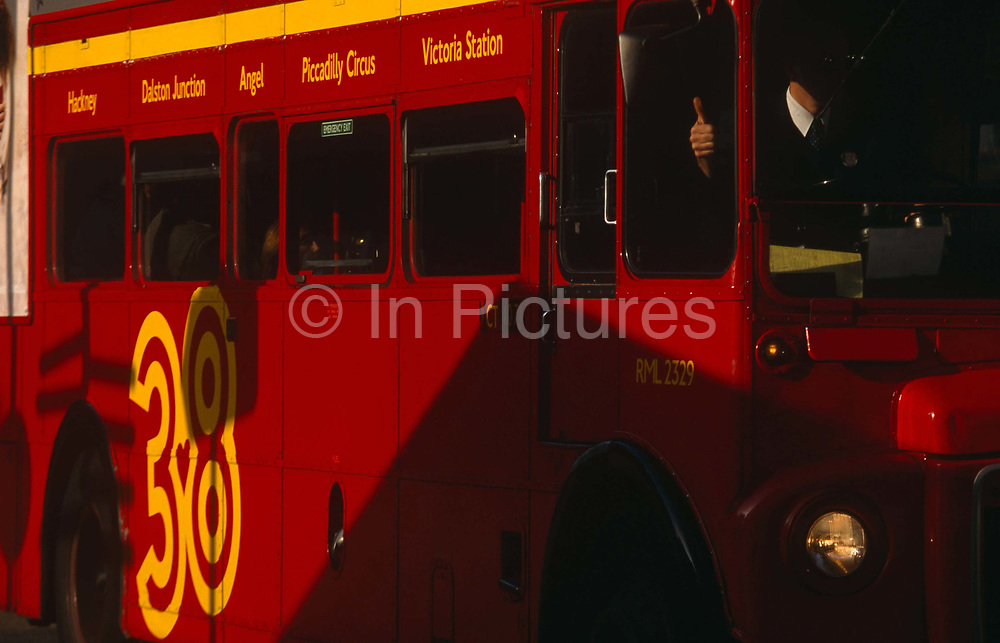 The unrecognisable driver of a number 38 red London bus which is passing between sunlight and shadow, gives a thumbs up signal to another road-user in the streets of Victoria. On the side of the vehicle's bodywork are the destinations the 38 route passes:  Hackney, Dalston Junction, Angel, Piccadilly Circus and Victoria Station. The bus is a traditional design called a Routemaster which has been in service on the capital's roads since 1954 and is nowadays only seen on heritage routes. From any angle, the bus is easily recognisable as that classic British transport icon.