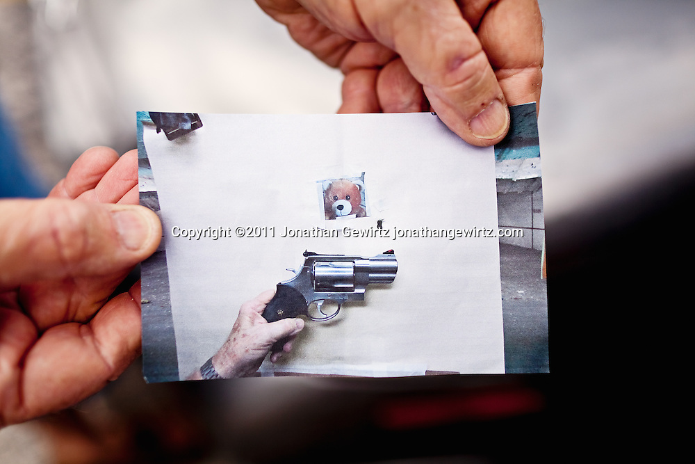 A shooter holds a cell phone photo showing his hand holding a handgun over a test target. The target has holes from two shots that are touching each other.. WATERMARKS WILL NOT APPEAR ON PRINTS OR LICENSED IMAGES.