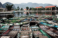 Small boats sit docked near the entryway to Tam Coc grottoes in Ninh Binh, northern Vietnam. The Tam Coc grottoes, with their winding waterways and limestone karst mountains, are a popular tourist attraction in the region.