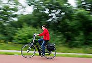 Een vrouw op een elektrische fiets rijdt bij Arnhem over het Rijn-Waalpad, de snelfietsroute tussen Arnhem en Nijmegen. Als de route helemaal klaar is, kunnen fietsers binnen 40 minuten van Arnhem naar Nijmegen fietsen. De snelfietsroute kent weinig obstakels en moet het aantrekkelijk maken om ook langere afstanden met de fiets af te leggen.<br /> <br /> Near Arnhem a woman is cycling on an electrical bike  the Rijn-Waalpad, the fast cycling route between Arnhem and Nijmegen.  When the route is finished, cyclists can get within 40 minutes from Arnhem to Nijmegen. The fast cycle route has few obstacles and to make it attractive to commute long distances by bicycle.