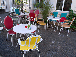 Colorful tables and chairs on street outside small cafe in bohemian district of Prenzlauer Berg in Berlin