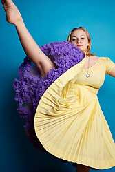 Young Woman Wearing Yellow Dress Lifting One Leg
