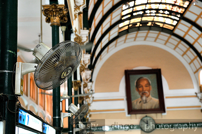 Interior of the Saigon Central Post Office (Buu Dien Truong Tam), with electric fan and large portrait of Ho Chi Minh. The Post Office was designed and built (1886--1891) by Gustave Eiffel, builder of the Eiffel Tower. Ho Chi Minh City (Saigon), Vietnam