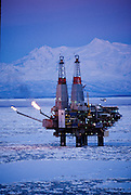 Alaska. Cook Inlet. An oil production platform's gas flares light up the winter sky near Mt Spurr.